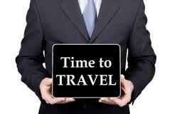 技术、互联网和网络在旅游业概念-拿着一台片剂个人计算机有时刻的商人旅行标志 库存照片