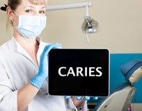 技术、互联网和网络在医学概念-拿着一台片剂个人计算机有龋的femail牙医签字 在 免版税库存图片