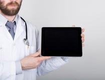 技术、互联网和网络在医学概念-篡改拿着一台片剂个人计算机有一个空白的黑暗的屏幕的 互联网 图库摄影