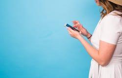 技术、人们和现代设备概念-接近在电话的妇女文字,在蓝色的短信的消息侧视图 免版税库存照片