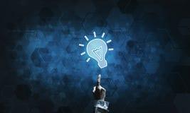 技术与发光的电灯泡象和接触它的想法概念手指 免版税库存图片