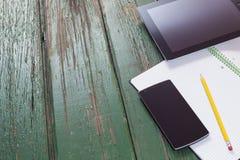 技术产品、电话和片剂在绿色木头与铅笔和笔记本 免版税库存图片