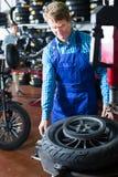 技术员人与摩托车的轮子一起使用 免版税图库摄影