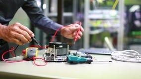 技术员使用测量螺丝刀和数字式多用电表的探针的人手检查和计算机mainboard电力电压  股票录像
