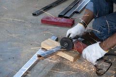 技术员使用磨床切开钢管 免版税库存照片