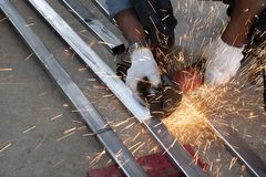 技术员使用磨床切开钢管 免版税库存图片