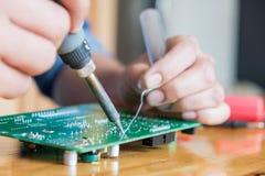 技术员修理电路板,在circu的用途焊接的设备 图库摄影