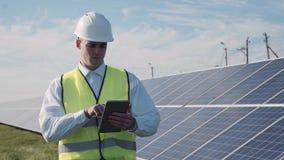 技术员在一些太阳电池板旁边走 库存图片