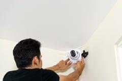 技术员在屋顶安装一台无线cctv照相机 库存图片