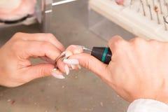 技术员在擦亮或研假肢或冠的一个牙齿实验室 免版税库存图片