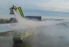 技术员在除冰飞机的机场 免版税库存照片