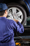 技术员填装的空气到在车库的车胎里 库存图片