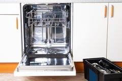 技术员工作的人们 有门户开放主义的一台残破的固定洗碗机在一个白色厨房和服务技术员工具箱里 免版税库存照片