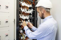 技术员工程师在数据中心连接光纤入通信开关 datacenter的服务人 免版税图库摄影