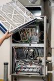 技术员插入新的熔炉过滤器入槽孔 库存照片