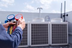 技术员检查空调,填装的空调的测量器材 免版税库存照片