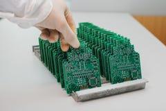 技术员采取与芯片的一个计算机板 备件和组分计算机设备的 生产  免版税库存照片