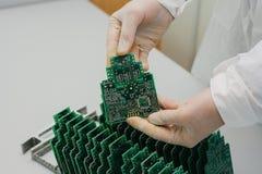 技术员采取与芯片的一个计算机板 备件和组分计算机设备的 生产  免版税图库摄影