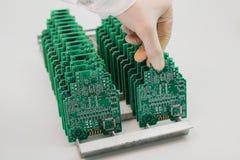 技术员采取与芯片的一个计算机板 备件和组分计算机设备的 生产  库存图片
