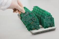 技术员采取与芯片的一个计算机板 备件和组分计算机设备的 生产  图库摄影