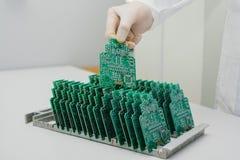 技术员采取与芯片的一个计算机板 备件和组分计算机设备的 生产  免版税库存图片
