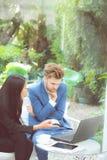 技术和办公室概念-两商人和妇女有膝上型计算机的 免版税库存图片