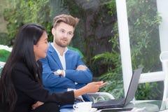 技术和办公室概念-两商人和妇女有膝上型计算机的 免版税库存照片
