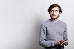技术和通信概念 有胡子的年轻时髦的人穿灰色毛线衣听到在白色耳机usi的音乐的 免版税库存照片