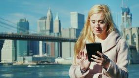 技术在大城市 享用板材的少妇以布鲁克林大桥和曼哈顿为背景 股票视频