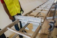 技术工程师检查在铝梯子的白锈病,风轮机塔的内部部分 免版税库存照片
