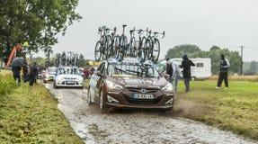 技术汽车-环法自行车赛行在一条被修补的路的2014年 免版税库存照片
