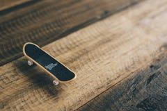技术甲板品牌手指滑板投入了木桌背景 库存照片