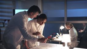 技术研究实验室:混合的族种运转与电子委员会的白色外套的电子工程师和