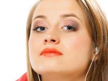 技术,音乐-耳机的青少年的女孩 免版税库存图片