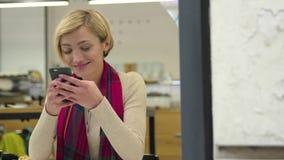 技术 使用手机的微笑的妇女在咖啡馆户内 股票录像