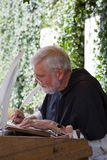 抄写员与他的纤管的修士文字 免版税库存照片