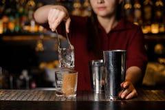 把一个大冰块放的男服务员女孩入一块空的玻璃在酒吧上 免版税库存照片