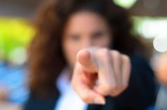 把一个控告手指指向的妇女照相机 免版税库存照片
