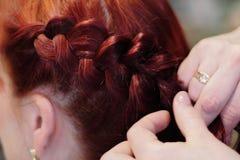 把一根` s头发,美发师工作编成辫子 免版税库存照片