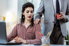 把他的手放的灰色服装的刚毅工友在女性同事上肩膀  免版税库存图片