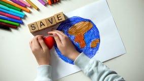 把保存词和心脏标志放的孩子在行星绘画,生态概念上 免版税图库摄影