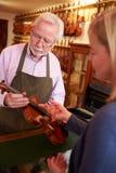 把修理的顾客小提琴留在商店 库存照片