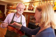 把修理的顾客小提琴留在商店 免版税库存图片