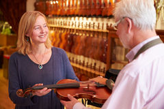 把修理的顾客小提琴留在商店 免版税库存照片