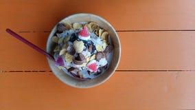 把冰放在一个杯子冷的面包条洒与顶部在一个木桌桔子上 免版税库存照片