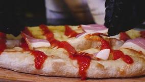 把切片火腿放的厨师在比萨上 ?? 烹调水多的可口意大利比萨用火腿和蒜味咸腊肠的特写镜头 ?? 影视素材