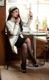 把唇膏放在她的嘴唇上和喝咖啡的黑白成套装备的时兴的少妇在餐馆 免版税库存照片