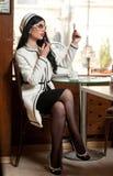 把唇膏放在她的嘴唇上和喝咖啡的黑白成套装备的时兴的少妇在餐馆 免版税库存图片