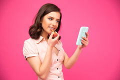把唇膏放的愉快的妇女在嘴唇上 免版税库存图片