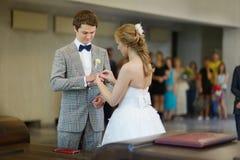 把圆环放的新娘在新郎的手指上 免版税库存图片